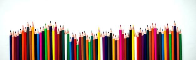 Rząd różnych kolorowych ołówków. tęczowe kredki poruszają się obok siebie. akcesoria szkolne, powrót do koncepcji szkoły. układ płaski.