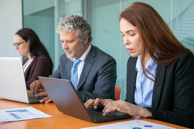 Rząd skupionych kolegów siedzących przy jednym stole i korzystających z komputerów