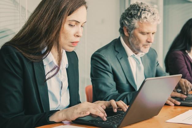 Rząd skupionych kolegów siedzących przy jednym stole i korzystających z komputerów.