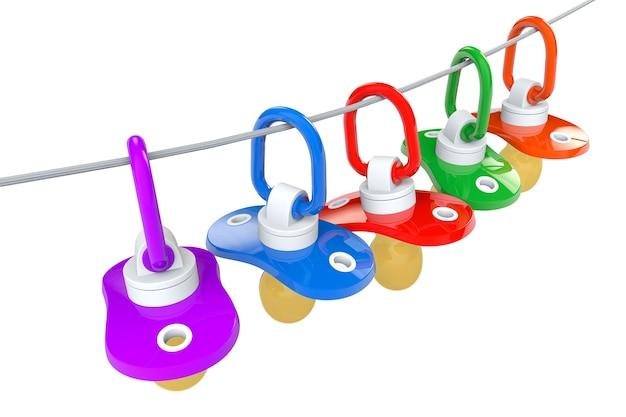 Rząd smoczków dla niemowląt ze sznurkiem na białym tle