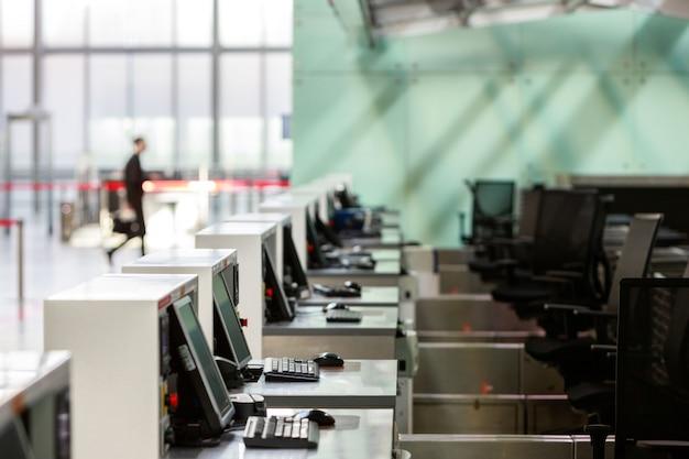 Rząd stanowisk odprawy z monitorami komputerowymi w pustym terminalu lotniska z powodu pandemii koronawirusa / epidemii covid-19