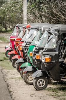 Rząd starannie zaparkowanych riksz tuk tuk auto.