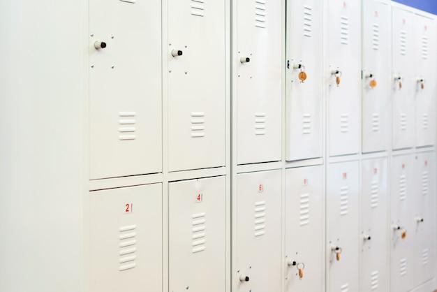 Rząd szafek szkolnych z szarego metalu z kluczami w drzwiach