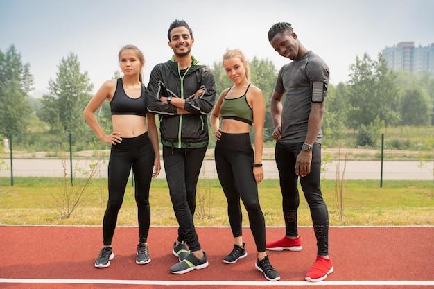 Rząd szczęśliwych młodych, międzykulturowych przyjaciół w odzieży sportowej, patrząc na ciebie na stadionie zewnętrznym w środowisku miejskim