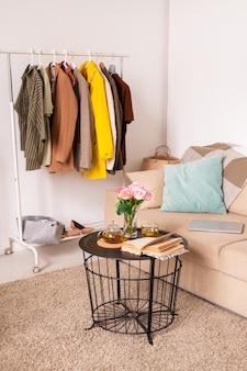 Rząd ubrań wiszących na wieszaku wzdłuż ściany przy wygodnej kanapie z poduszkami i stolikiem z książką, różami i herbatą ziołową