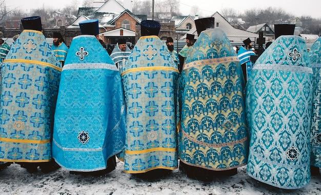 Rząd ukraińskich księży kościelnych w pięknych sutannach ze znakami krzyża