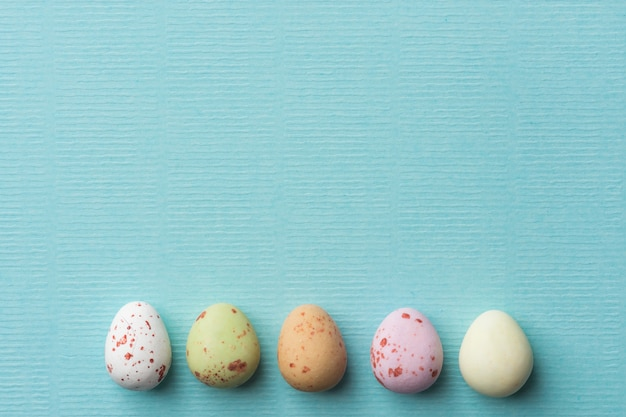 Rząd wielobarwny nakrapiane czekoladowe pisanki na jasnoniebieskim tle turkusu