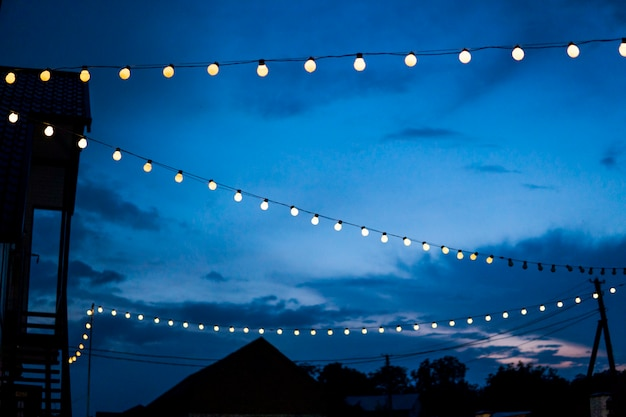 Rząd wiszących letnich tarasowych świateł wieczorem, małe zewnętrzne żarówki.