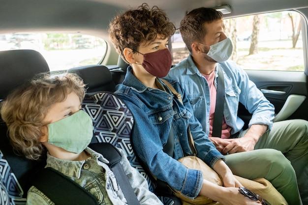 Rząd współczesnej młodej trzyosobowej rodziny w ochronnych maskach i dżinsowych kurtkach, patrząc do przodu jadąc samochodem na tylnym siedzeniu