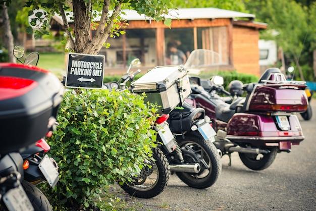 """Rząd z zaparkowanymi motocyklami na polu kempingowym ze znakiem """"tylko parkowanie motocykla""""."""