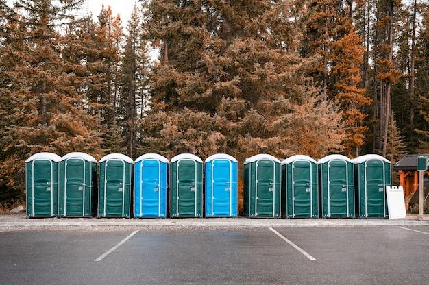 Rząd zielonych, niebieskich przenośnych toalet chemicznych w jesiennym lesie w parku narodowym