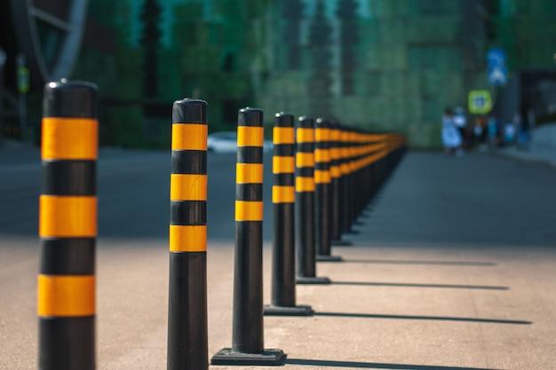 Rząd żółtych barier na drodze, oddzielających linie ruchu i strefę dla pieszych.