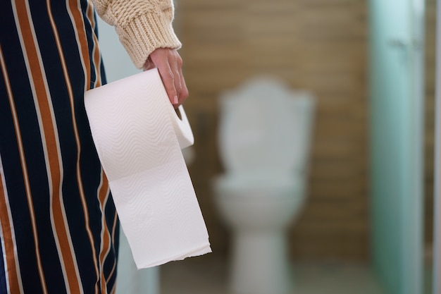 Rzadki widok kobiety mienia rolki papieru toaletowego przed toaletą.