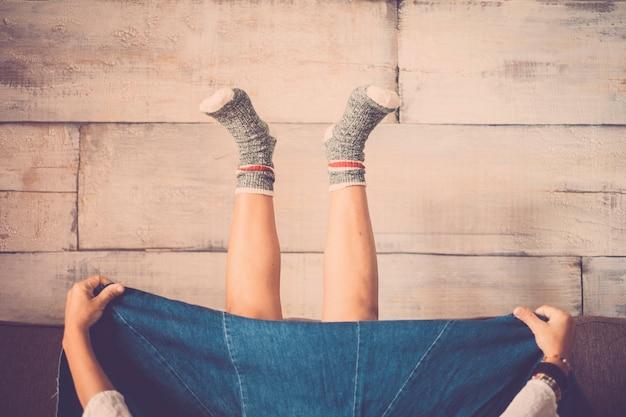 Rzadki widok nogi kobiety z dużą dżinsową spódnicą w domu w odwrotnej pozycji od ziemi do góry ze szczęśliwymi ciepłymi skarpetkami i drewnianą ścianą - koncepcja szaleństwa i szczęścia