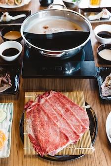 Rzadkie plastry wołowiny wagyu a5 na maty bambusowej z czarną płytą do gotowania w gorącej puli shabu.