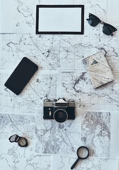 Rzecz, której potrzebujesz w podróży. ujęcie pod dużym kątem okularów przeciwsłonecznych, aparatu fotograficznego, kompasu, szkła powiększającego