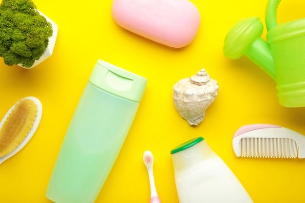 Rzeczy dla niemowląt leżące na płasko. gąbka, mydło, żel pod prysznic, gumowa kaczuszka, grzebień na żółto. kosmetyki dla niemowląt z widokiem z góry