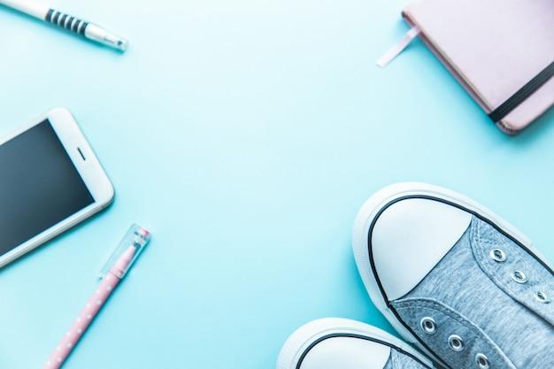Rzeczy nastolatka modnisia notepad telefonu sneakers mieszkanie kłaść na błękitnym tle. koncepcja powrotu do szkoły.