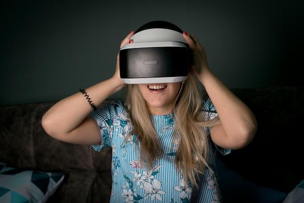 Rzeczywistość wirtualna vr. dziewczyna chce zdobyć doświadczenie w okularach zestawu słuchawkowego vr. niesamowite emocje, fajny odpoczynek, restart. okulary wirtualnej rzeczywistości leżą w neonowych światłach. pojęcie rzeczywistości wizualnej