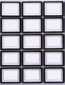 Rzędy czarnych ramek na białych ścianach