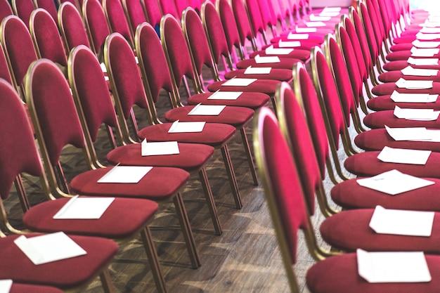 Rzędy czerwonych krzeseł w sali konferencyjnej, pustej sali spotkań lub sali imprez. puste miejsca dla gości.