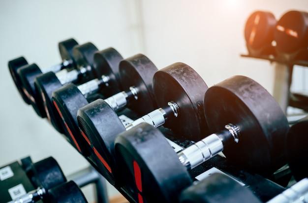 Rzędy hantli na siłowni.