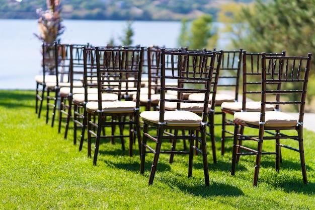 Rzędy krzeseł dla gości podczas ceremonii ślubnej na świeżym powietrzu.