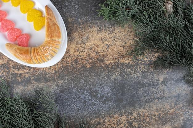 Rzędy marmolady i półksiężycowa bułka na talerzu między sosnowymi gałęziami na drewnianej powierzchni