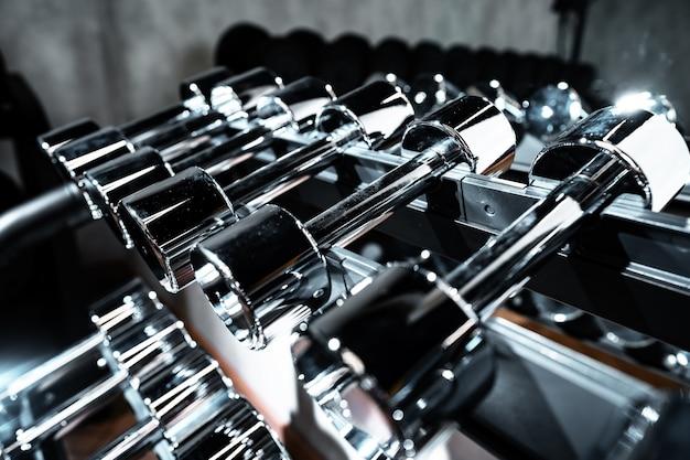 Rzędy metalowych hantli na stojaku do kulturystyki na siłowni