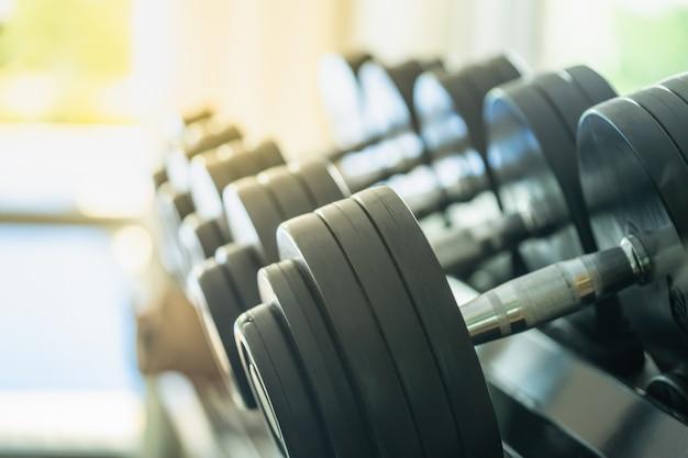 Rzędy metalowych hantli na stojaku w siłowni lub klubie sportowym.