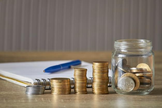 Rzędy monety i słój monety na drewnianym stole z szarym tłem, pieniądze oszczędzania pojęcie