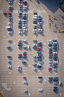 Rzędy na samochodach na dużym parkingu w pobliżu supermarketu. parking w pobliżu supermarketu. widok z lotu ptaka