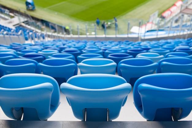 Rzędy niebieskich miejsc na stadionie piłkarskim.