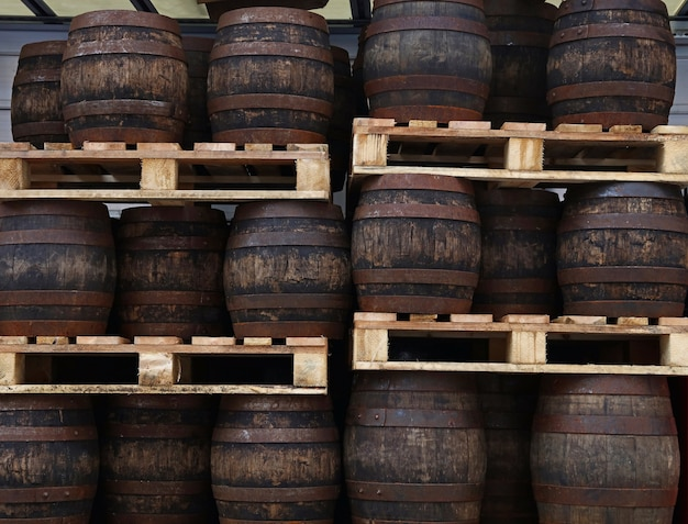Rzędy palet z postawionymi starymi beczkami z ciemnego drewna dębowego w stylu grunge z piwem rzemieślniczym w magazynie browaru