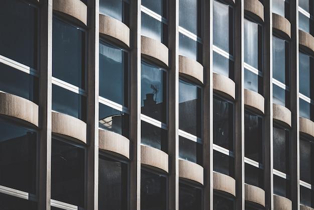 Rzędy pionowych okien na elewacji biurowca