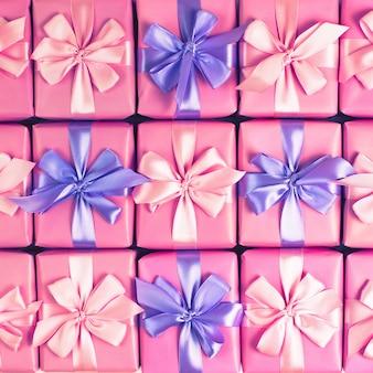 Rzędy pudełek z prezentami dekoracja wstążka satynowa kokardka różowy widok z góry z płaskim położyć tonowanie