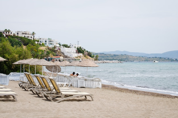 Rzędy pustych leżaków i parasoli na plaży. camel beach w turcji.