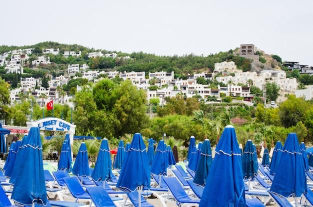 Rzędy pustych niebieskich leżaków i parasoli na plaży. camel beach w turcji.