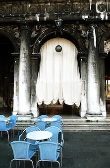 Rzędy pustych stołów i krzeseł w kawiarni na świeżym powietrzu.