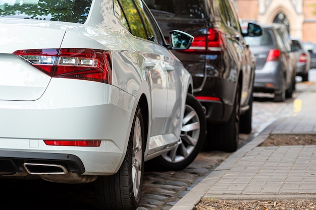 Rzędy różnych samochodów zaparkowanych na poboczach zatłoczonego miasta