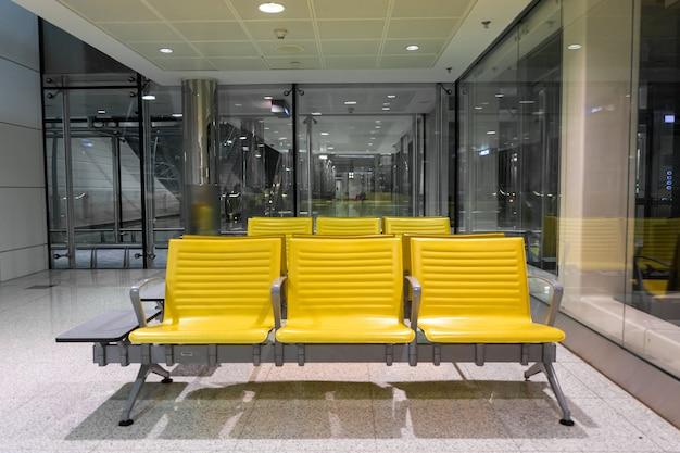 Rzędy żółtych ławek w poczekalni na lotnisku.