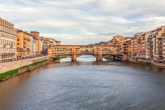Rzeka arno prowadząca do słynnego mostu ponte vecchio w piękny wieczór we florencji we włoszech