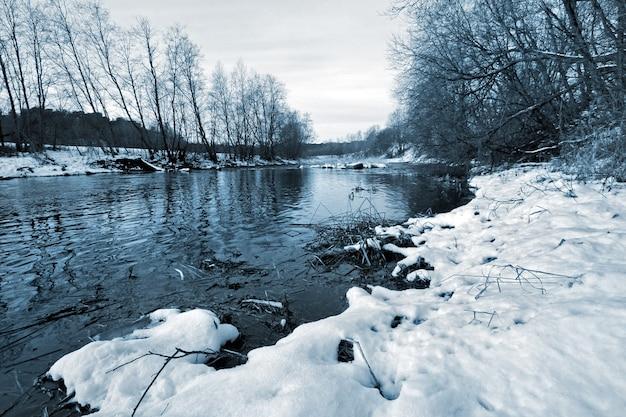 Rzeka bez lodu w zimie ze śniegiem na brzegu