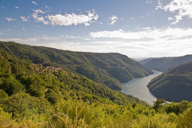 Rzeka minho otoczona wzgórzami pokrytymi zielenią w słońcu w hiszpanii