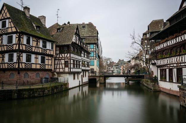 Rzeka otoczona budynkami w petite france pod zachmurzonym niebem w strasburgu we francji