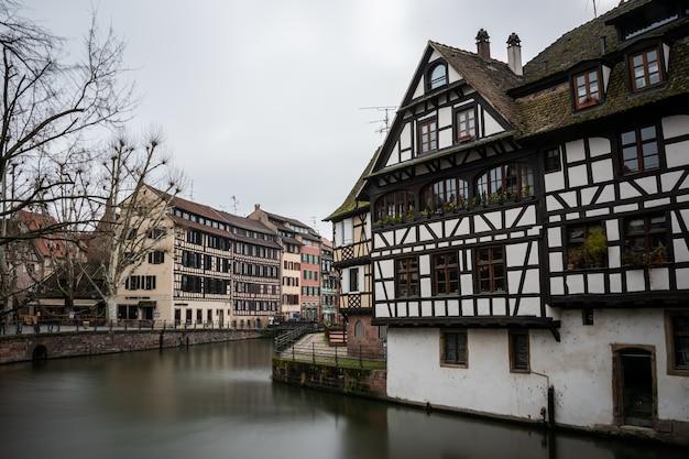 Rzeka otoczona kolorowymi budynkami i zielenią pod zachmurzonym niebem w strasburgu we francji