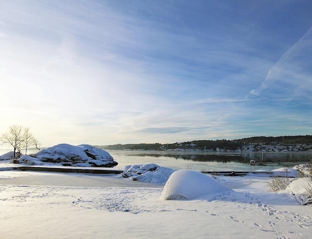 Rzeka otoczona skałami i domami pokrytymi śniegiem w słońcu w larvik w norwegii