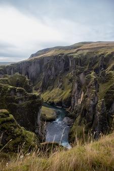 Rzeka otoczona skałami pokrytymi zielenią i suchą trawą pod pochmurnym niebem