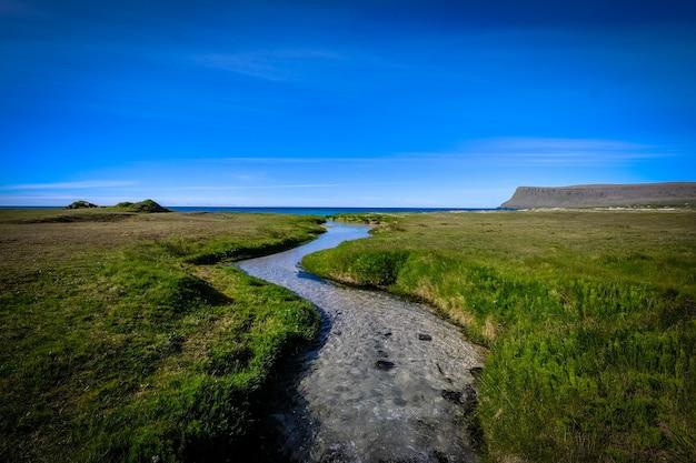 Rzeka pośrodku trawiastego pola pod jasnym niebieskim niebem