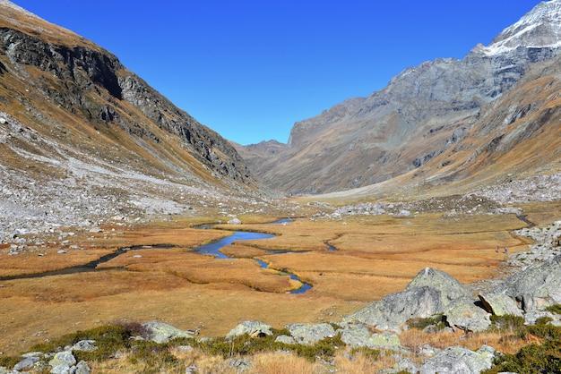 Rzeka przecinająca dolinę między skalistymi górami na żółtej trawie jesienią i pod niebem